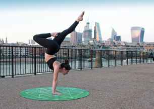woman wearing black top and leggings on green yoga mat